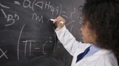 4K Portrait of happy smiling little scientist writing math formula on blackboard - stock footage