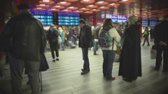 Crowd of passengers waiting in railway station hall, checking train timetables Stock Footage