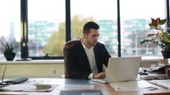 Man in jacket works for laptop Stock Footage