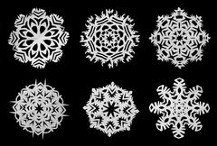 Snowflakes cut out of paper on a black background - stock photo