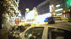 Police car at mass protest site, officer patrolling crowded city street at night Stock Footage