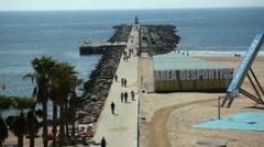 People walk on jetty boardwalk Portimao beach, Algarve, Portugal, Atlantic Stock Footage