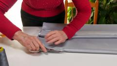 Dressmaker Cutting and Folding Clothes with Scissors Stock Footage