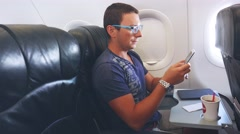 Young handsome businessman with tablet sitting inside an airplane. Young male Stock Footage