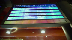 Close-up of blue display screen with train timetables at busy railway station Stock Footage