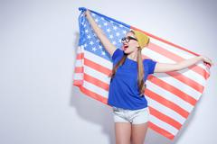 Cheerful young woman is expressing her patriotism - stock photo