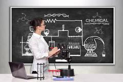 Female scientist looking on scheme chemical reaction Stock Photos