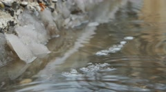 Spring puddle with ice and dropping water. Diagonal composition. Place for text - stock footage