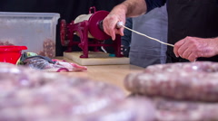 Putting the intestine on a sausage maker on a kitchen counter - stock footage