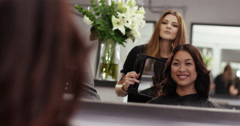 An attractive young woman at a salon checking her hair in the mirror. - stock footage
