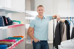 Portrait of confident salesman leaning on rack in clothing store - stock photo