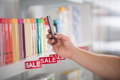 Closeup photo of customer photographing cosmetic product arranged on shelf in - stock photo