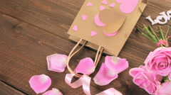 Pink roses with chocolates on rustic wood table. Stock Footage