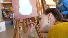 Female artist paints picture artwork in art studio - stock footage