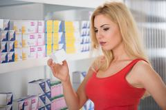 Young woman examining capsule packet at pharmacy - stock photo
