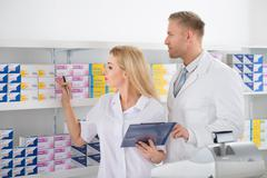 Male and female pharmacists checking inventory at pharmacy Kuvituskuvat