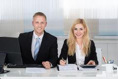 Portrait of smiling male and female accountants calculating finance at desk i - stock photo