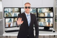 Portrait of security manager gesturing stop sign against monitors in office - stock photo