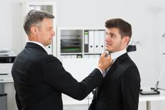 Side view of angry mature businessman gripping employee's tie in office Stock Photos