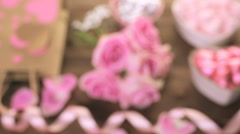 Stock Video Footage of Pink roses with chocolates on rustic wood table.
