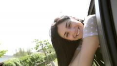 Happy girl enjoying air from car window smiling Arkistovideo