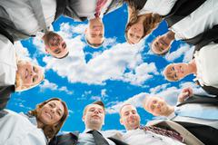 Stock Photo of Directly below portrait of diverse business people forming huddle against sky