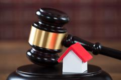 Closeup of wooden mallet with house model on table in courtroom - stock photo