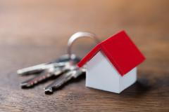 Closeup of house model and keys on wooden table - stock photo