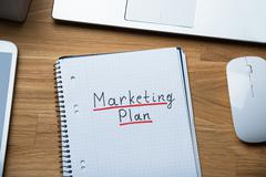 High angle view of marketing plan written on notepad at office desk - stock photo