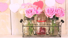 Bouquet with pink roses in mason jar on wood shelf. Stock Footage