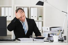 Tensed male accountant sitting with head in hand at desk in office Stock Photos
