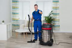 Full length portrait of janitor showing thumbs up while holding vacuum cleane - stock photo