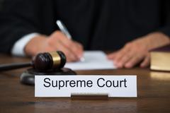 Supreme court nameplate with judge writing on paper at table in courtroom Kuvituskuvat