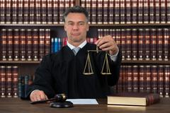 Mature male judge holding justice scale at table against bookshelf in courtro - stock photo