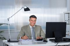 Portrait of smiling accountant using calculator while writing on documents at Stock Photos