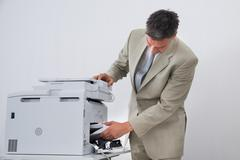 Mature businessman removing paper stuck in printer at office - stock photo