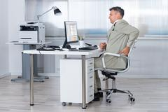 Side view of accountant suffering from back pain at desk in office Stock Photos