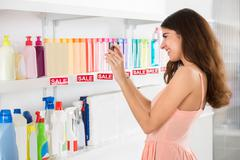 Side view of smiling female customer photographing cosmetic products on shelf - stock photo