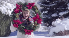 Teen Plays With Christmas Wreath, Hides Behind It, Peeks Out, Wears It And Waves Stock Footage