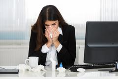 Sick young businesswoman blowing her nose at computer desk in office Stock Photos