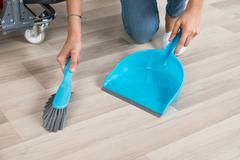 Cropped image of female cleaner sweeping wooden floor with small broom and du Stock Photos