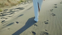 Feet of woman walking on beach dunes in white dress while sun drops shadow - stock footage
