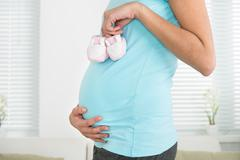 Midsection of pregnant woman holding baby shoes at home - stock photo