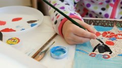 Child paints watercolor picture with paint brush Stock Footage