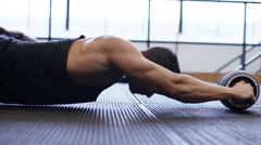 Strong young man using an ab roller in the gym Stock Footage