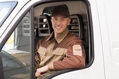 Stock Photo of Portrait of confident delivery man smiling in truck