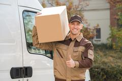 Stock Photo of Portrait of young delivery man carrying cardboard box on shoulder with truck
