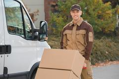 Portrait of confident delivery man pushing parcels on handtruck against van Stock Photos