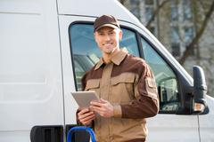 Stock Photo of Portrait of smiling delivery man holding digital tablet against truck