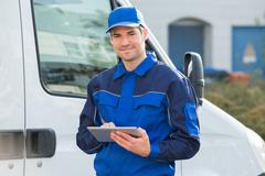 Portrait of delivery man smiling using digital tablet by truck Stock Photos